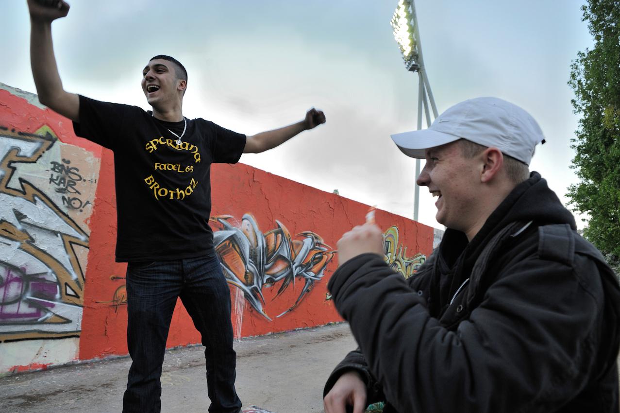 Jugendliche vor mit Graffiti besprühter inneren Mauer, im Hintergrund Flutlichtmast des Cantian-Stadions.